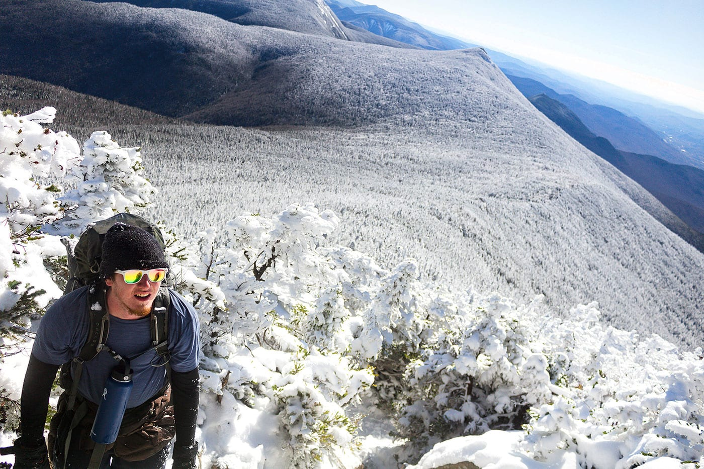 A photo of a man hiking snowy Franconia Notch as he recovers from addiction with help from Foxhole Immersion.